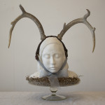 """The gifted child"" - Air-dry clay, antlers, moss, ribbon, glass stand, 45x43x37 cm, 2013"